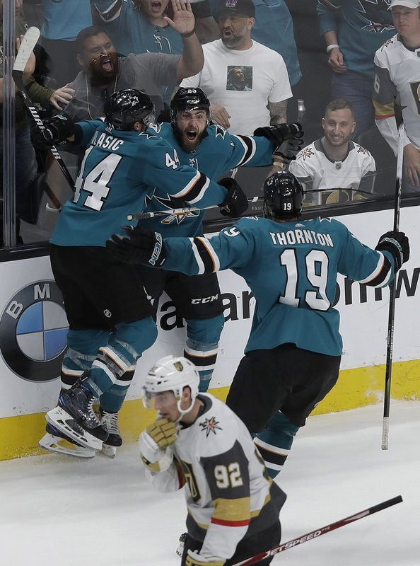 San Jose Sharks right wing Barclay Goodrow, center, is congratulated by defenseman Marc-Edouard Vlasic (44) and center Joe Thornton (19) after scoring the winning goal against the Vegas Golden Knights during overtime of Game 7 of an NHL hockey first-round playoff series in San Jose, Calif. (92). (AP Photo/Jeff Chiu)