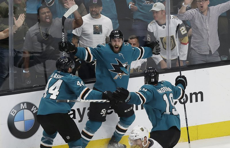 San Jose Sharks right wing Barclay Goodrow, center, celebrates with defenseman Marc-Edouard Vlasic (44) and center Joe Thornton (19) after scoring the winning goal against the Vegas Golden Knights during overtime of Game 7 of an NHL hockey first-round playoff series in San Jose, Calif. (AP Photo/Jeff Chiu)