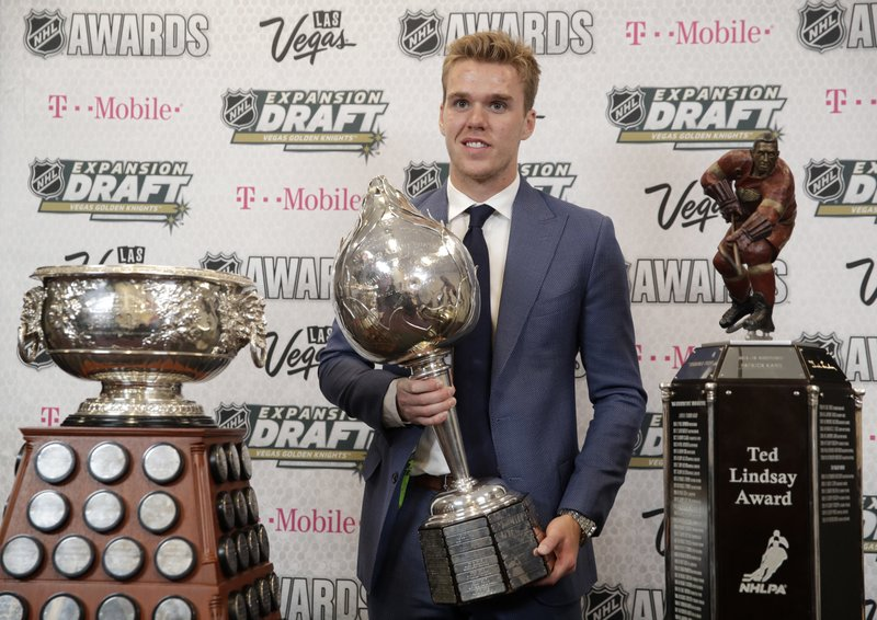 FILE - In this Wednesday, June 21, 2017 file photo, Connor McDavid of the Edmonton Oilers poses with the Art Ross Trophy, left, the Hart Memorial Trophy, center, and the Ted Lindsay Award after winning the honors during the NHL Awards in Las Vegas. (AP Photo/John Locher, File)