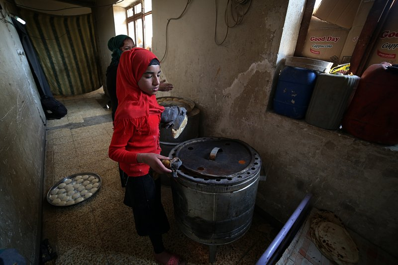 In this March 18, 2019 photo, Um Yusuf, a widow of an Islamic State group militant, and her daughter make bread to sell, in Mosul, Iraq. (AP Photo/Farid Abdulwahed)