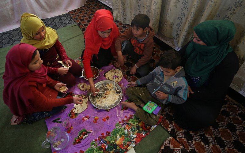In this March 18, 2019 photo, Um Yusuf, a widow of an Islamic State group militant, and her children have lunch, in Mosul, Iraq. (AP Photo/Farid Abdulwahed)
