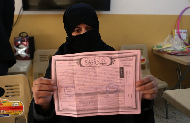 In this Feb. 26, 2019 photo, a widow of Islamic State group militant, Muthanna Hussein, who was killed fighting Iraqi security forces, displays her husband's death certificate, issued by IS, at a legal clinic supported by the Norwegian Refugee Council, in west Mosul, Iraq. (AP Photo/Khalid Mohammed)