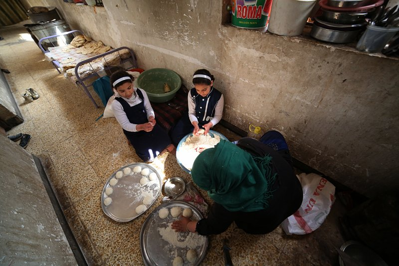 In this March 18, 2019 photo, Um Yusuf, a widow of an Islamic State group militant, and her daughters make bread to sell, in Mosul, Iraq. (AP Photo/Farid Abdulwahed)