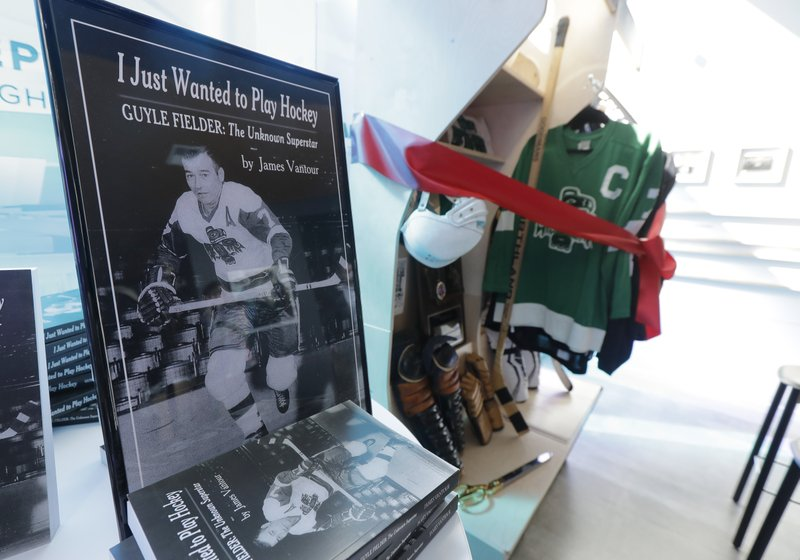 A book about the life of Guyle Fielder, who played for the Seattle Totems in the Western Hockey League, is displayed Tuesday, April 23, 2019, in Seattle in front of a locker-room style display of some of Fielder's hockey memorabilia from his playing days. (AP Photo/Ted S. Warren)