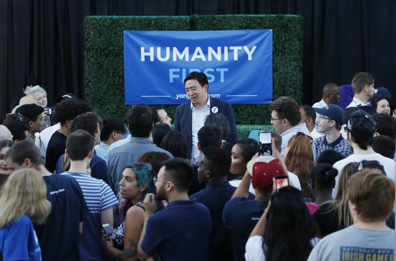 Democratic presidential candidate and entrepreneur Andrew Yang, center, meets with people at a campaign event Tuesday, April 23, 2019, in Las Vegas. (AP Photo/John Locher)