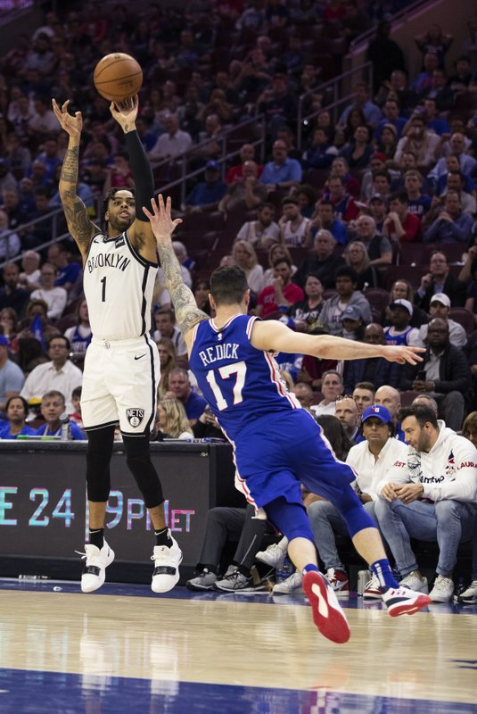 Brooklyn Nets' D'Angelo Russell, left, shoots the ball with Philadelphia 76ers' JJ Redick, right, defending during the second half in Game 5 of a first-round NBA basketball playoff series, Tuesday, April 23, 2019, in Philadelphia. (AP Photo/Chris Szagola)