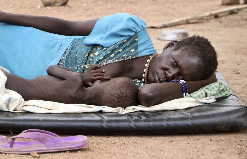 In this photo taken Wednesday, April 17, 2019, Agiu Nyang, 1, who is sick with measles, is nursed by his mother Amel Makir as she lies on the ground at the hospital in Kuajok, South Sudan. (AP Photo/Sam Mednick)