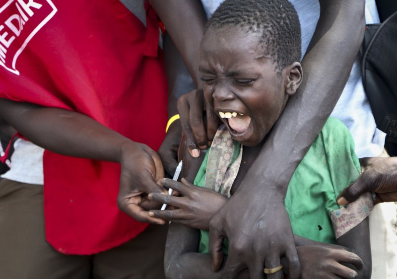 In this photo taken Wednesday, April 17, 2019, a boy yells as a community health worker vaccinates him against measles outside of Kuajok, South Sudan. (AP Photo/Sam Mednick)