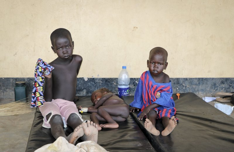 In this photo taken Wednesday, April 17, 2019, three children with measles lie on mats outside the hospital in Kuajok, South Sudan. (AP Photo/Sam Mednick)