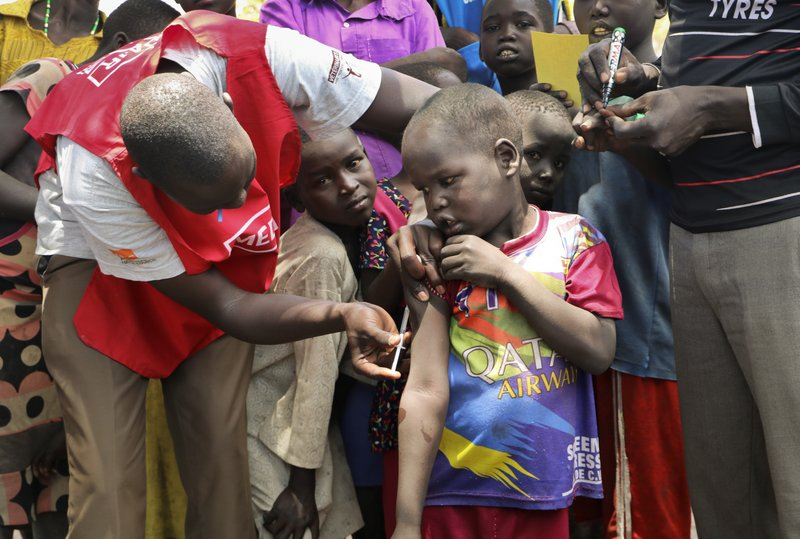 In this photo taken Wednesday, April 17, 2019, a community health worker vaccinates children against measles outside of Kuajok, South Sudan. (AP Photo/Sam Mednick)