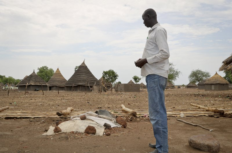 In this photo taken Wednesday, April 17, 2019, John Garang Ajak stands in his yard looking at the grave of his nephew who died in March after contracting measles, in Kuajok, South Sudan. (AP Photo/Sam Mednick)