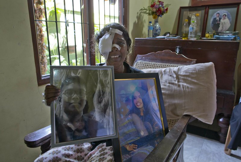 Anusha Kumari holds portraits of her daughter Sajini Venura Dulakshi and son Vimukthi Tharidu Appuhami, both victims of Easter Sunday's bomb blast in Negombo, Sri Lanka, Wednesday, April 24, 2019. (AP Photo/Gemunu Amarasinghe)