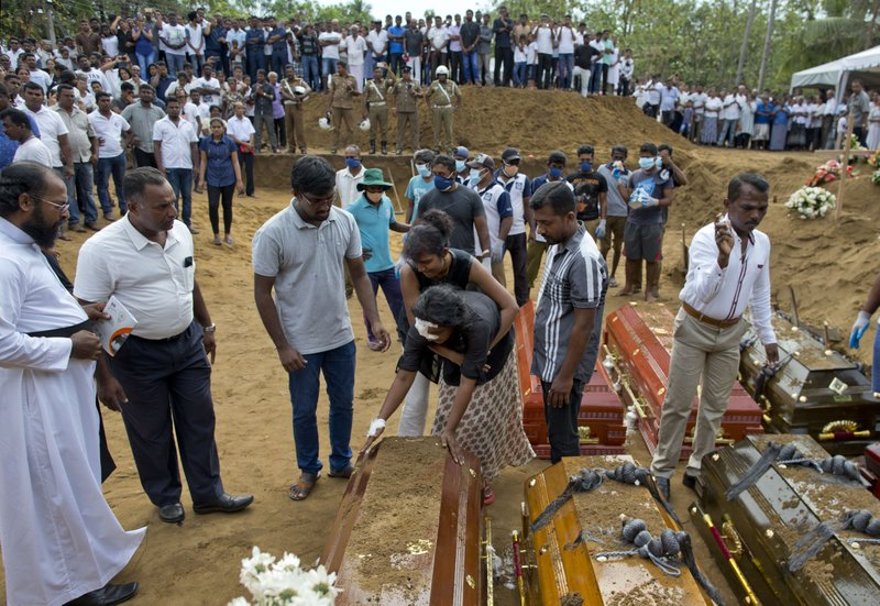 Anusha Kumari, center, holds a coffin during a mass burial for her husband, two children and three siblings, all victims of Easter Sunday's bomb blast in Negombo, Sri Lanka, Wednesday, April 24, 2019. (AP Photo/Gemunu Amarasinghe)