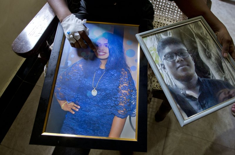 Anusha Kumari holds portraits of her daughter Sajini Venura Dulakshi and son Vimukthi Tharidu Appuhami, both victims of Easter Sunday's bomb explosion, in Negombo, Sri Lanka, Wednesday, April 24, 2019. (AP Photo/Gemunu Amarasinghe)