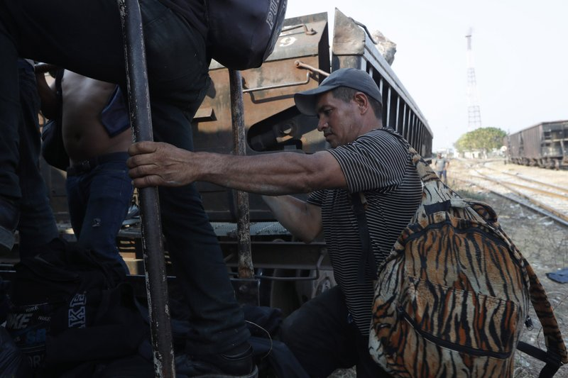 A Central American migrant climbs on a freight train on is way to the U.S.-Mexico border, in Ixtepec, Oaxaca state, Mexico, Tuesday, April 23, 2019. (AP Photo/Moises Castillo)