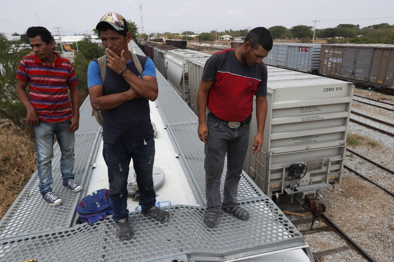 Honduran migrants Jose Francisco Mendez, left, Denis Funes, center, and Jose Mendoza stand on top of a freight train during their journey toward the U. (AP Photo/Moises Castillo)