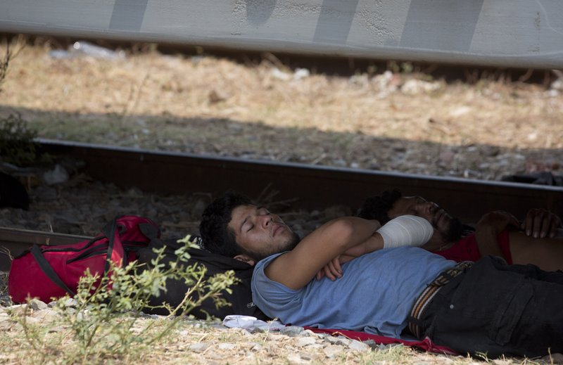 A Central American migrant takes a nap in the shade under a freight train car, during his journey toward the US-Mexico border, in Ixtepec, Oaxaca State, Mexico, Tuesday, April 23, 2019. (AP Photo/Moises Castillo)
