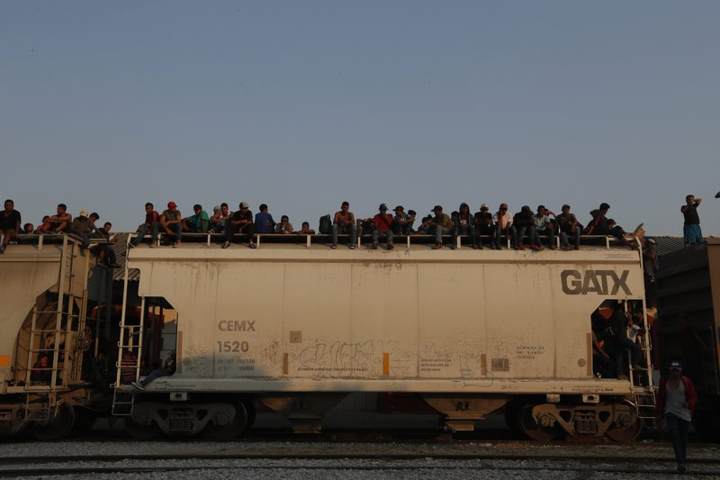 Central American migrants ride atop a freight train during their journey toward the US-Mexico border, in Ixtepec, Oaxaca State, Mexico, Tuesday, April 23, 2019. (AP Photo/Moises Castillo)
