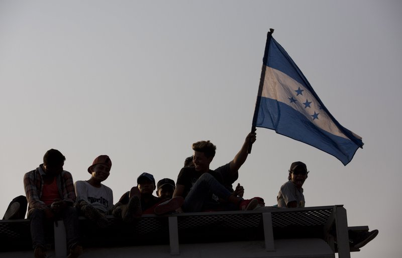 Honduran migrants flying their country's flag, ride atop a freight train during their journey toward the US-Mexico border, in Ixtepec, Oaxaca State, Mexico, Tuesday, April 23, 2019. (AP Photo/Moises Castillo)