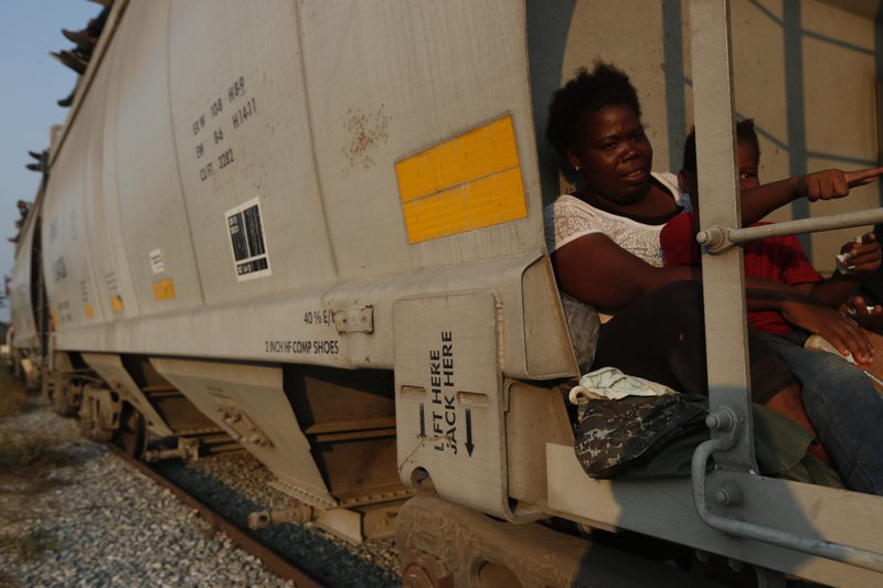 A woman and her son, from Roatan, Honduras, ride on a north-bound freight train on their way to the U. (AP Photo/Moises Castillo)