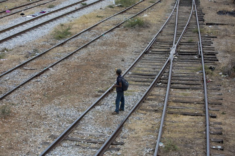 A Central American migrant waits on the train tracks during his journey toward the US-Mexico border, in Ixtepec, Oaxaca State, Mexico, Tuesday, April 23, 2019. (AP Photo/Moises Castillo)