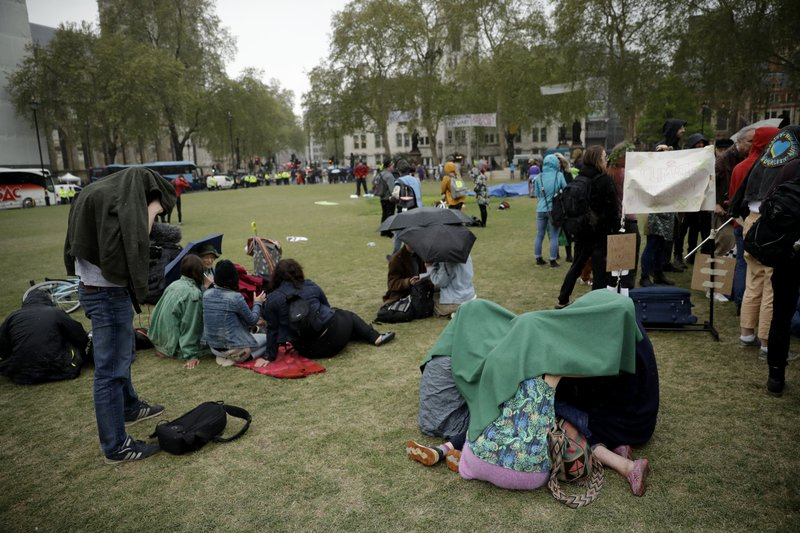 Extinction Rebellion climate change protesters shelter from a rain shower as they stand on Parliament Square in London, Wednesday, April 24, 2019. (AP Photo/Matt Dunham)