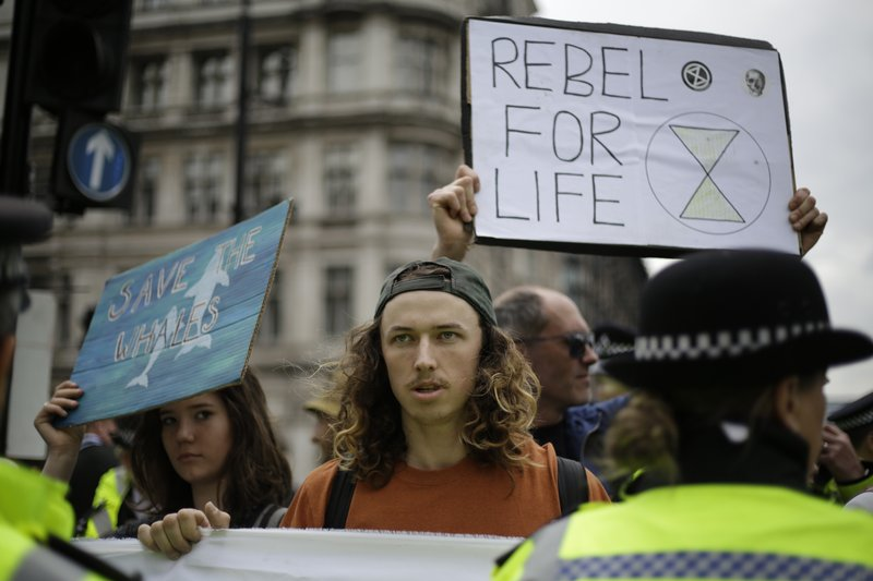 Extinction Rebellion climate change protesters hold banners as they briefly block traffic around Parliament Square in central London, Wednesday, April 24, 2019. (AP Photo/Matt Dunham)