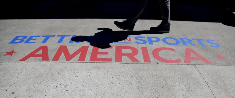 An attendee walks near a logo outside of the Meadowlands Exposition Center during the Betting On Sports America conference, Wednesday, April 24, 2019, in Secaucus, N. (AP Photo/Julio Cortez)
