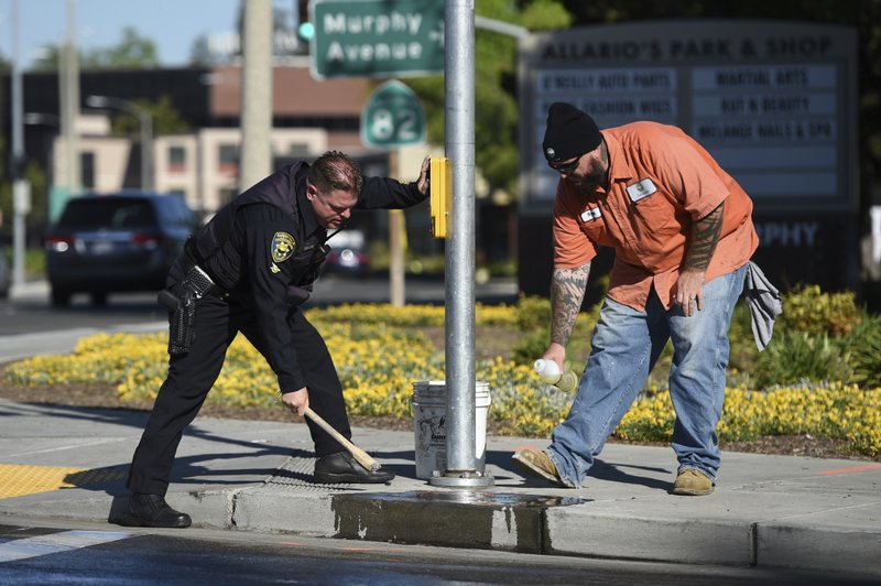 Police and road crews work to clean up the scene after a car crash at the intersection of El Camino Real and Sunnyvale Road in Sunnyvale, Calif. (AP Photo/Cody Glenn)