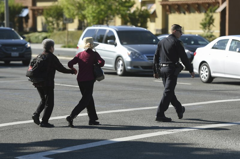 A police officer escorts pedestrians across El Camino Real near the scene of car crash at the intersection of El Camino Real and Sunnyvale Road in Sunnyvale, Calif. (AP Photo/Cody Glenn)