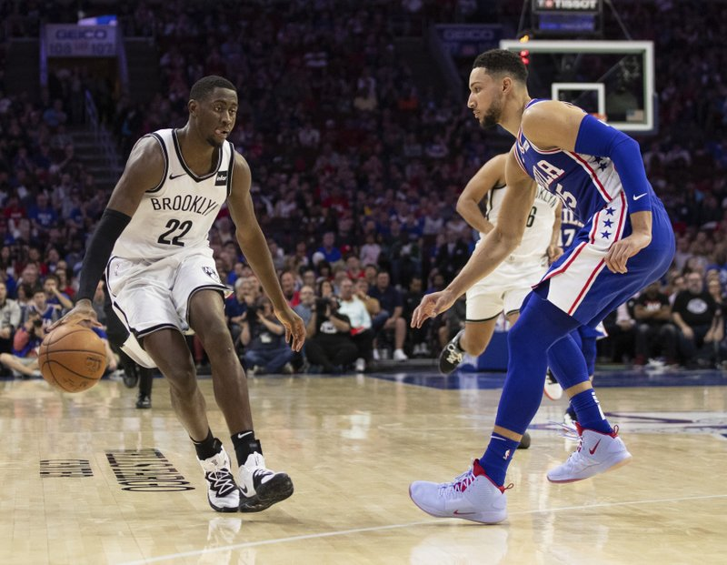 Brooklyn Nets' Caris LeVert, left, makes his move against Philadelphia 76ers' Ben Simmons, right, of Australia, during the second half in Game 5 of a first-round NBA basketball playoff series, Tuesday, April 23, 2019, in Philadelphia. (AP Photo/Chris Szagola)
