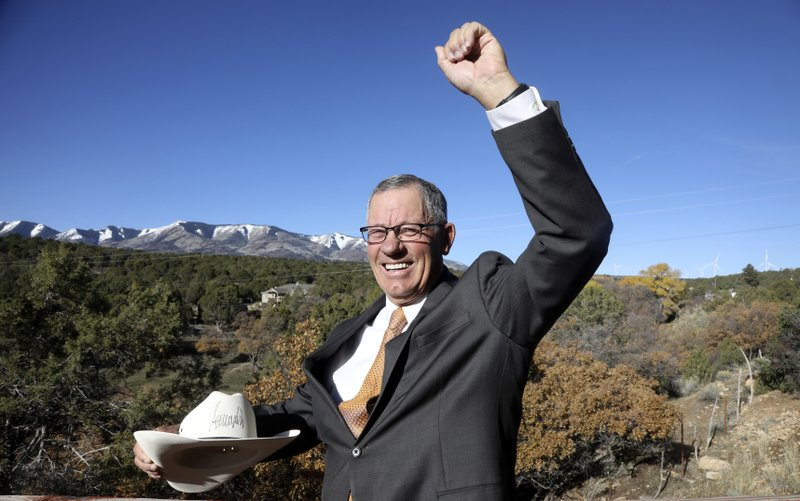 FILE - In this Oct. 26, 2018 file photo, Bruce Adams, Republican chair of the San Juan County commission, poses with the hat signed by President Donald Trump after signing a proclamation to shrink the size of Bears Ears and Grand Staircase Escalante national monuments at his home in Monticello, Utah. (AP Photo/Rick Bowmer, File)