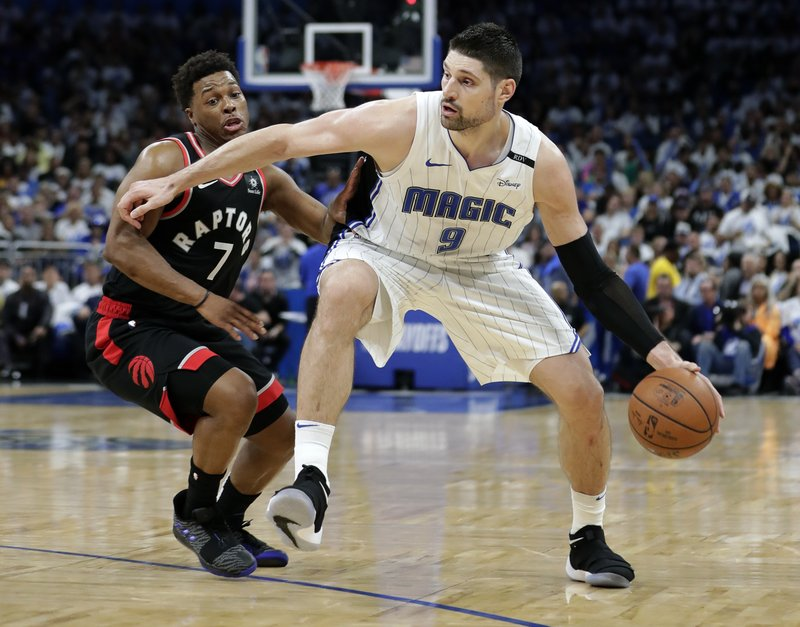 Orlando Magic's Nikola Vucevic (9) moves the ball against Toronto Raptors' Kyle Lowry (7) during the second half in Game 3 of a first-round NBA basketball playoff series, Friday, April 19, 2019, in Orlando, Fla. (AP Photo/John Raoux)