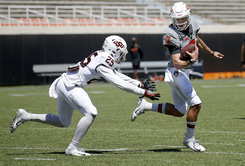 Oklahoma State's Spencer Sanders (3) gets by Jason Taylor II (25) during a two-minute drill during NCAA college spring football practice in Stillwater, Okla. (Sarah Phipps/The Oklahoman via AP)