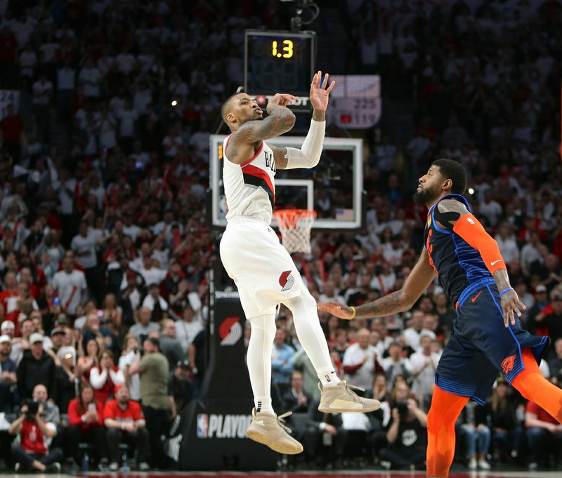 Portland Trail Blazers' Damian Lillard watches his game-winning three-pointer as Oklahoma City Thunder' Paul George defends, to beat the  Thunder 118-115 in Game 5 of their best-of-seven first-round playoff series in Portland, Ore. (Sean Meagher/The Oregonian via AP)