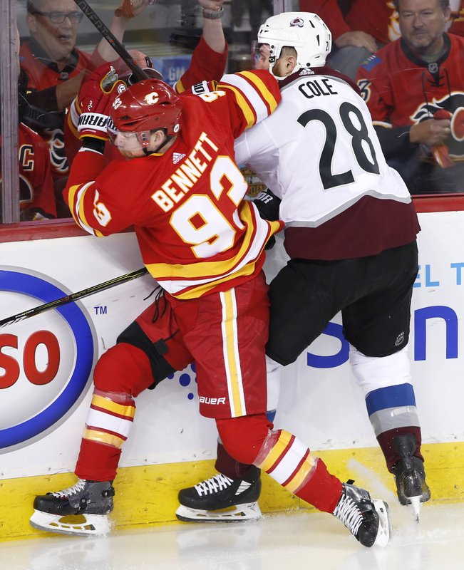 Colorado Avalanche defenseman Ian Cole (28) takes a hit from Calgary Flames center Sam Bennett (93) during the first period of Game 5 of an NHL hockey first-round playoff series Friday, April 19, 2019, in Calgary, Alberta. (Larry MacDougal/The Canadian Press via AP)