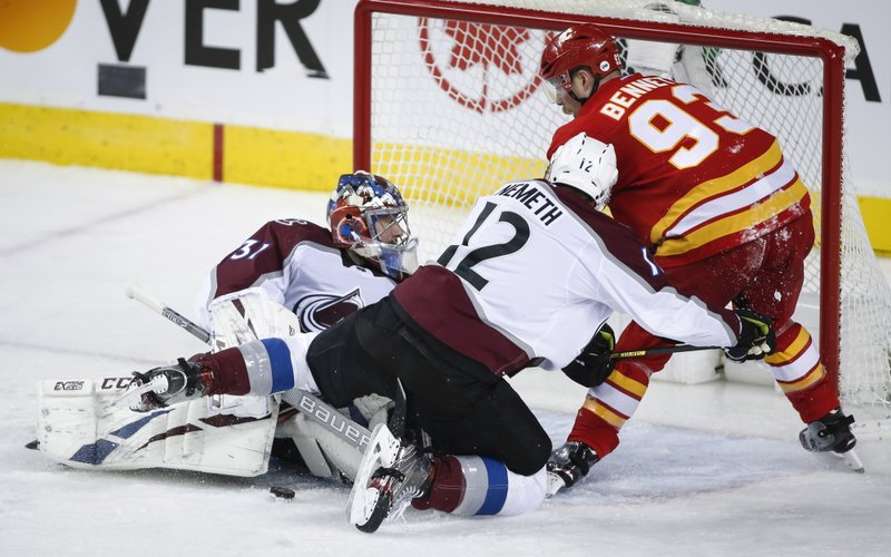 Colorado Avalanche's Patrik Nemeth, center, pushes Calgary Flames' Sam Bennett away from Avalanche goalie Philipp Grubauer during the second period of Game 2 of an NHL hockey first-round playoff series Saturday, April 13, 2019, in Calgary, Alberta. (Jeff McIntosh/The Canadian Press via AP)