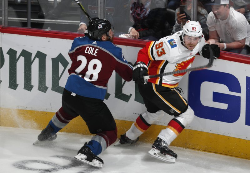 Colorado Avalanche defenseman Ian Cole, left, uses his stick to slow Calgary Flames center Sam Bennett who pursues the puck in the first period of Game 3 of a first-round NHL hockey playoff series Monday, April 15, 2019, in Denver. (AP Photo/David Zalubowski)