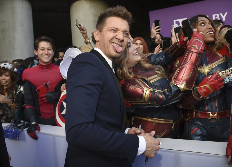Jeremy Renner takes a selfie with a fan as he arrives at the premiere of