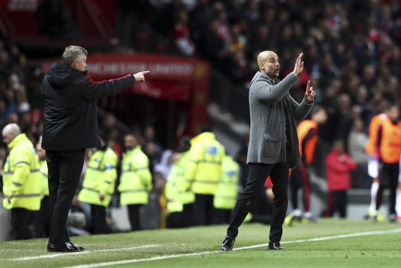 Manchester United manager Ole Gunnar Solskjaer, left, and Manchester City coach Pep Guardiola gesture during the English Premier League soccer match between Manchester United and Manchester City at Old Trafford Stadium in Manchester, England, Wednesday April 24, 2019. (AP Photo/Jon Super)