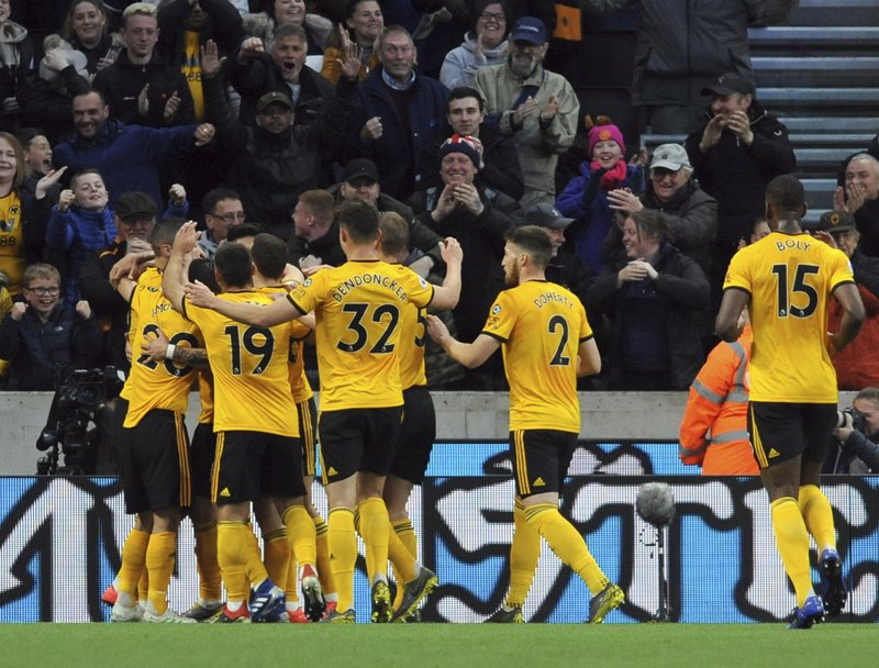 Wolverhampton's Ruben Neves celebrates with teammates after scoring his side's opening goal during the English Premier League soccer match between Wolverhampton Wanderers and Arsenal at the Molineux Stadium in Wolverhampton, England, Wednesday, April 24, 2019. (AP Photo/Rui Vieira)