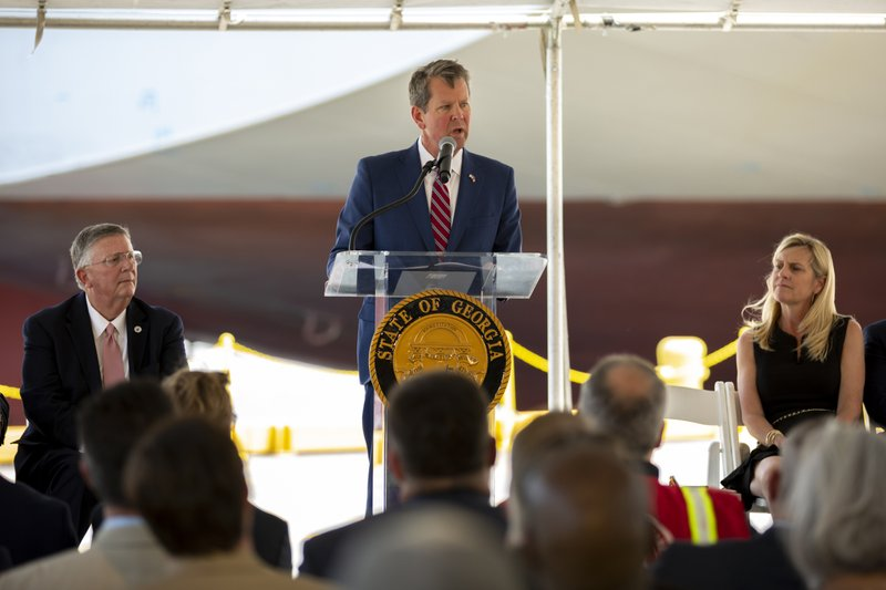 In this photo provided by the Georgia Port Authority, Georgia Governor Brian Kemp, center, joins the Georgia Department of Economic Development, the Savannah Economic Development Authority, Georgia Ports Authority and Plastic Express, Wednesday, April 24, 2019, to announce that Plastic Express will bring 166 high wage jobs and, along with Capital Development Partners, $172 million in investment to the region at an event at the Garden City Terminal at the Port of Savannah in Savannah, Ga. (Stephen Morton/Georgia Ports Authority via AP)