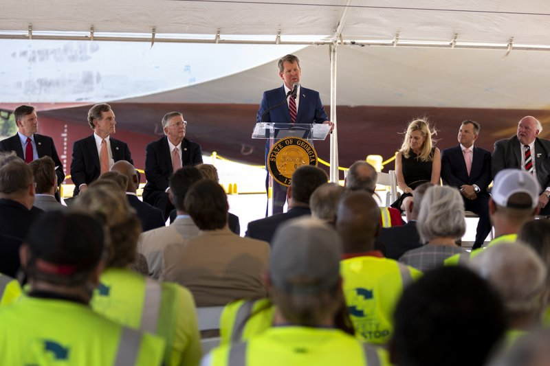 In this photo provided by the Georgia Port Authority, Georgia Governor Brian Kemp, center, joined the Georgia Department of Economic Development, the Savannah Economic Development Authority, Georgia Ports Authority and Plastic Express, Wednesday, April 24, 2019, to announce that Plastic Express will bring 166 high wage jobs and, along with Capital Development Partners, $172 million in investment to the region at an event at the Garden City Terminal at the Port of Savannah in Savannah, Ga. (AP Photo/Georgia Port Authority, Stephen Morton)