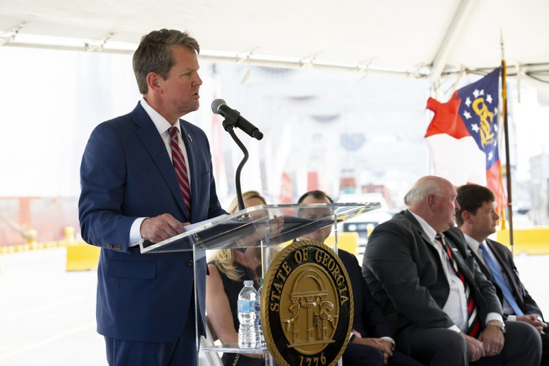 In this photo provided by the Georgia Port Authority, Georgia Governor Brian Kemp, left, joins the Georgia Department of Economic Development, the Savannah Economic Development Authority, Georgia Ports Authority and Plastic Express, Wednesday, April 24, 2019, to announce that Plastic Express will bring 166 high wage jobs and, along with Capital Development Partners, $172 million in investment to the region at an event at the Garden City Terminal at the Port of Savannah in Savannah, Ga. (AP Photo/Georgia Port Authority, Stephen Morton)