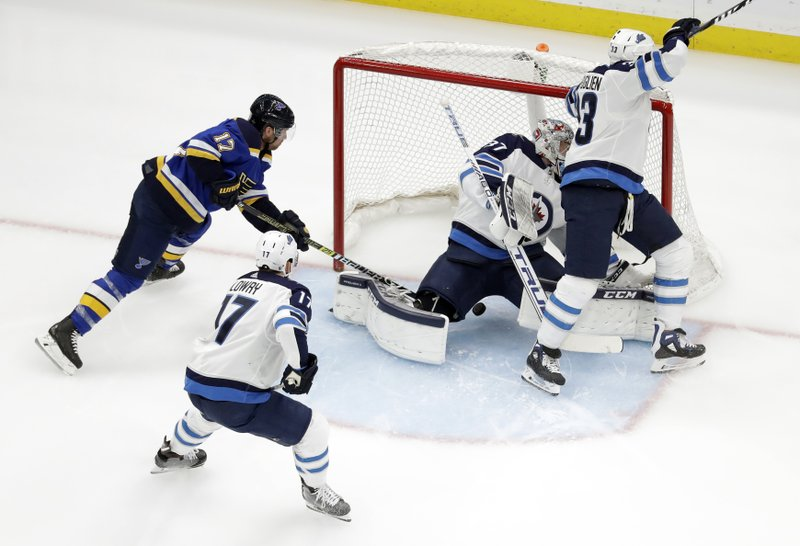St. Louis Blues' Jaden Schwartz (17) scores past Winnipeg Jets goaltender Connor Hellebuyck, Dustin Byfuglien (33) and Adam Lowry (17) during the first period in Game 6 of an NHL first-round hockey playoff series, Saturday, April 20, 2019, in St. (AP Photo/Jeff Roberson)