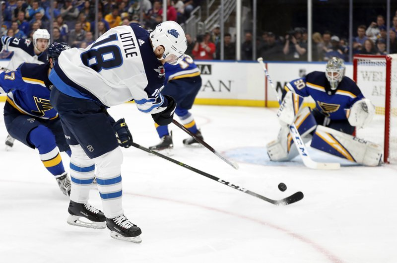 Winnipeg Jets' Bryan Little (18) shoots toward St. Louis Blues goaltender Jordan Binnington during the first period in Game 6 of an NHL first-round hockey playoff series, Saturday, April 20, 2019, in St. (AP Photo/Jeff Roberson)