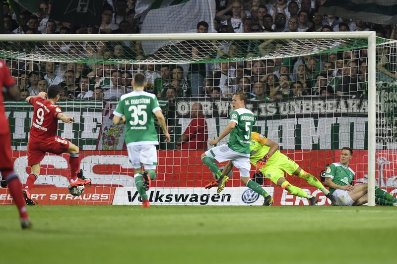 Bayern's Robert Lewandowski, left, scores his side's first goal passing Bremen goalkeeper Jiri Pavlenka during the German soccer cup, DFB Pokal, semifinal match between Werder Bremen and Bayern Munich at the Weser stadium in Bremen, Germany, Wednesday, April 24, 2019. (AP Photo/Martin Meissner)