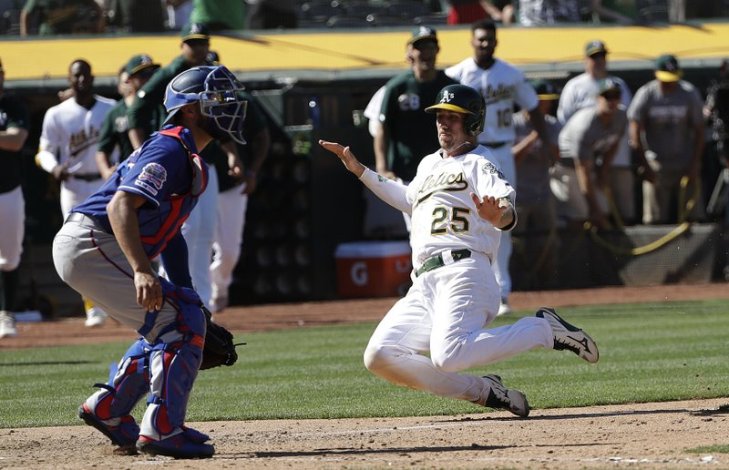 Oakland Athletics' Stephen Piscotty (25) slides in to home to score the winning run as Texas Rangers catcher Isiah Kiner-Falefa, left, waits for the throw during the ninth inning of a baseball game in Oakland, Calif. (AP Photo/Jeff Chiu)
