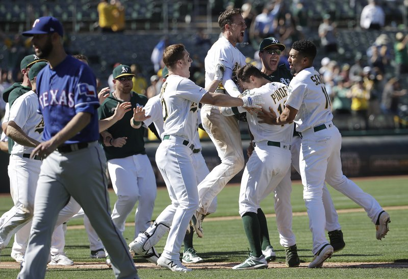 Oakland Athletics' Chad Pinder, second from right, is congratulated by teammates after driving in the winning run against the Texas Rangers during the ninth inning of a baseball game in Oakland, Calif. (AP Photo/Jeff Chiu)