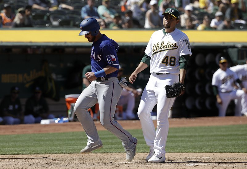 Texas Rangers' Jeff Mathis, left, scores a run past Oakland Athletics pitcher Joakim Soria (48) during the seventh inning of a baseball game in Oakland, Calif. (AP Photo/Jeff Chiu)